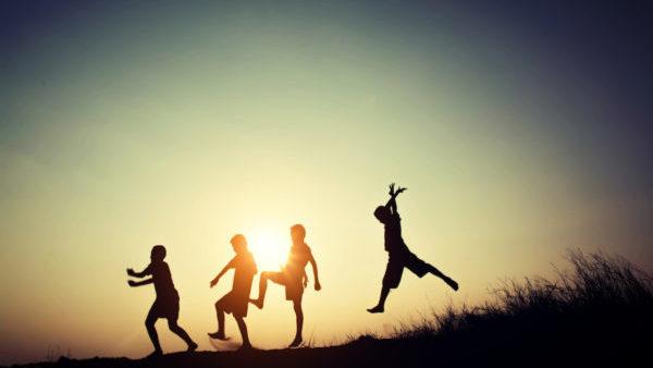 Niños jugando de frente a un atardecer